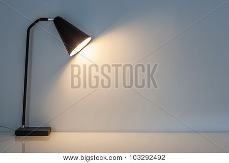 The Modern Desk Lamp Illuminate On The Wall Background.