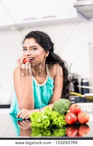 Indian woman eating healthy apple in her kitchen, salad and vegetables on the counter