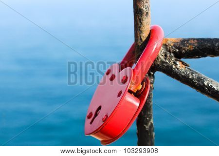 red padlock in shape of a heart on the background of the sea