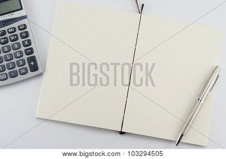 Opened notepad with pen and calculator.