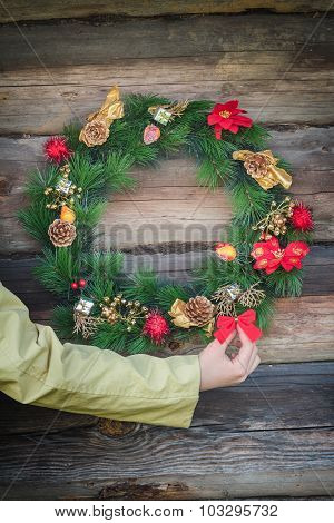 Woman Arm Holding Red Bow And Decorating Outdoor Log Cabin Wall With X-mas Wreath
