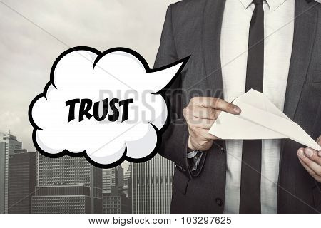 Trust text on speech bubble with businessman holding paper plane in hand