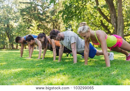 fitness, sport, friendship and healthy lifestyle concept - group of teenage friends or sportsmen exercising and doing push-ups at boot camp