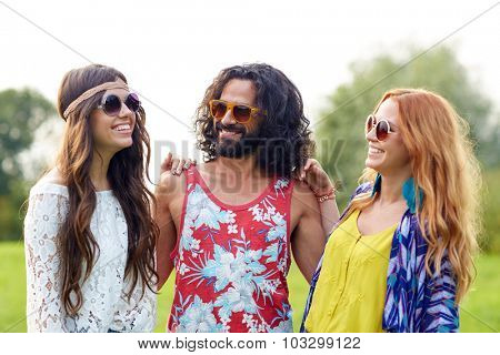 nature, summer, youth culture and people concept - smiling young hippie friends in sunglasses talking outdoors