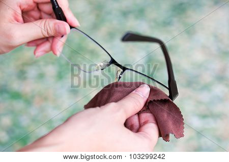 Women Hand Cleaning Glasses Lens With Blur Green Background..