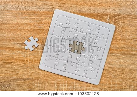 Piece Missing From Jigsaw Puzzle On Wooden Table