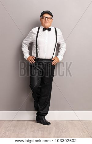 Full length portrait of a fashionable senior gentleman with black suspenders and bow-tie leaning against a wall and looking at the camera