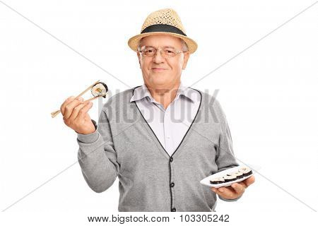 Joyful senior gentleman holding a piece of sushi and looking at the camera isolated on white background