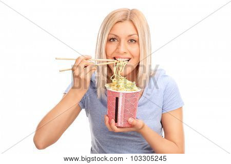 Beautiful blond woman eating Chinese noodles with sticks and looking at the camera isolated on white background