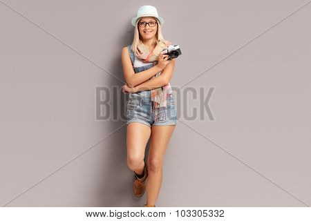 Blond female photographer with a blue hat holding a camera and leaning against a gray wall