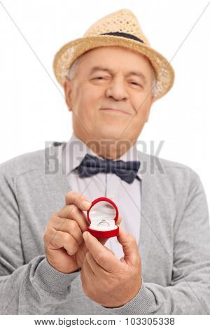 Vertical shot of a romantic senior gentleman proposing with an engagement ring isolated on white background with the focus on the ring