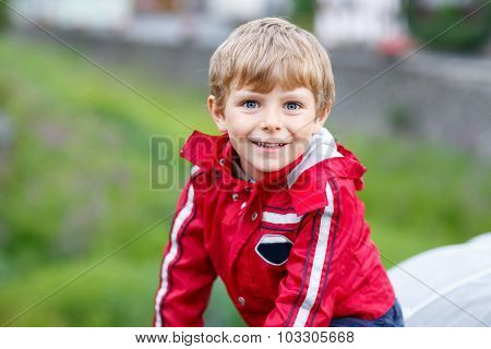 Portrait Of Little Schoolboy Outdoors On Rainy Day