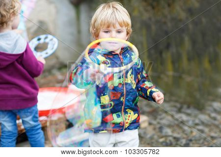 Child Boy Blowing Soap Bubbles Outdoor