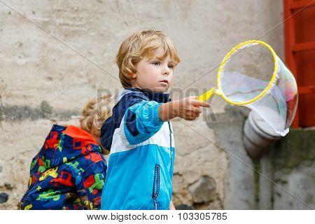 Child Boy Blowing Soap Bubbles Outdoor