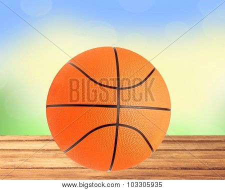 Basketball Ball On The Table Over Bight Nature Background