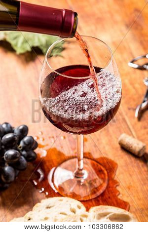 Pouring red wine glass against wooden background