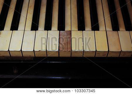 Closeup of black and white piano keys and wood grain with vintage sepia tone one ragged keys