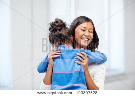 family, children, love and happy people concept - happy mother and daughter hugging at home