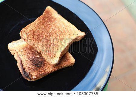 Slice Toasted Bread On Black Dish.