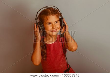 Girl European appearance decade listening to music with headphon