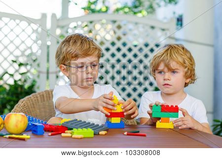 Two Little Kid Boys Playing With Plastic Blocks Together