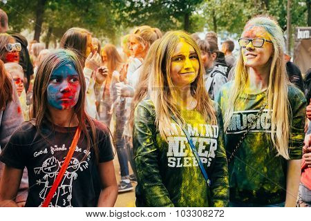 Young people having fun and dancing together at Holi color festi