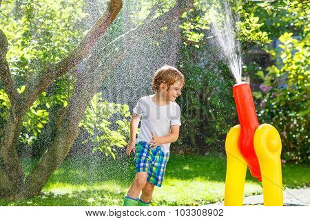 Little Kid Boy Playing  With A Garden Hose And Water