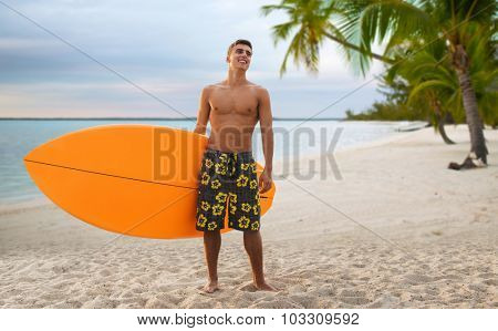 summer vacation, people, travel and water sport concept - smiling young man with surfboard or stand up paddle board over tropical beach and palm trees beach background