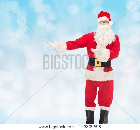 christmas, holidays, gesture and people concept - man in costume of santa claus over blue lights background