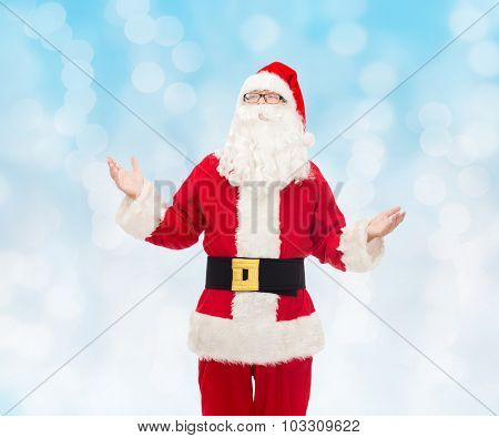 christmas, holidays and people concept - man in costume of santa claus over blue lights background