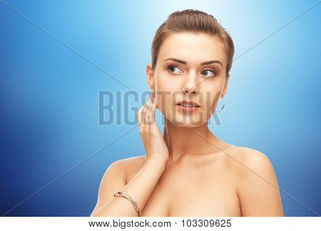 beauty, luxury, people, holidays and jewelry concept - beautiful woman wearing gold earrings and bracelet over blue background