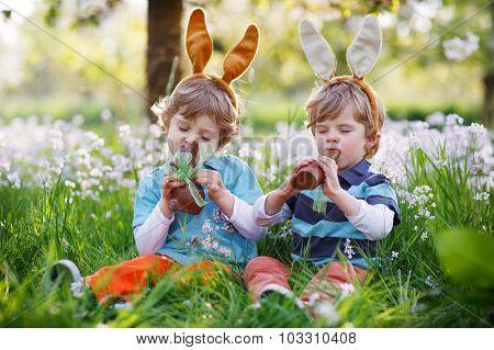Sibling Boys In Easter Bunny Ears Eating Chocolate