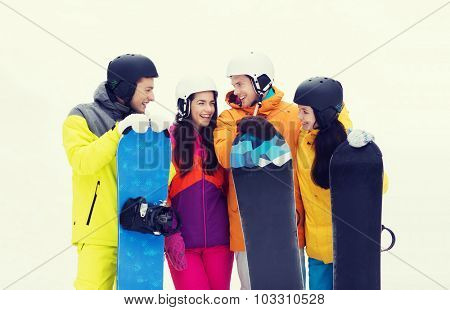 winter, leisure, extreme sport, friendship and people concept - happy friends in helmets with snowboards talking