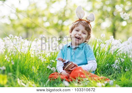 Cute Happy Little Boy Wearing Easter Bunny Ears And Eating Choco