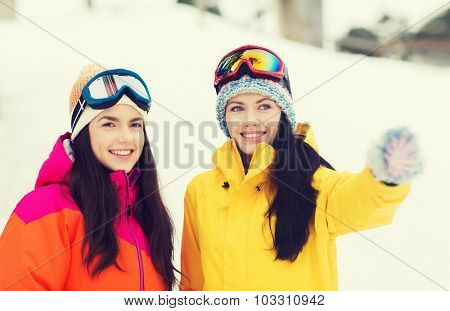 winter, leisure, sport, friendship and people concept - happy girl friends in ski goggles outdoors