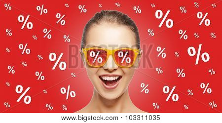 people, summer, shopping and sale concept - happy screaming teenage girl in shades over red background with percentage signs