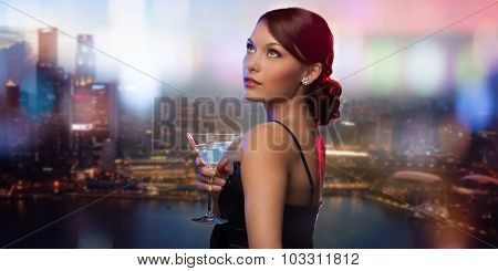 party, drinks, holidays, luxury and celebration concept - smiling woman in evening dress holding cocktail over night city background