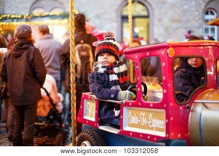 Little Boy On A Carousel At Christmas Market, Outdoors