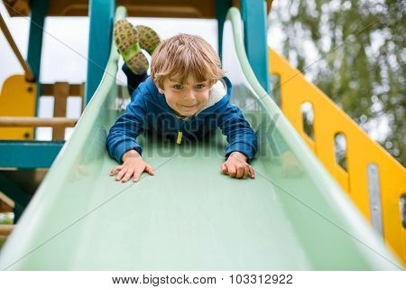 Kid Boy Having Fun And Sliding On Outdoor Playground