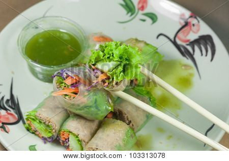 Portion Of Spring Rolls On Old Wood With Spicy Sauce, Vegetables And In Noodle Tube