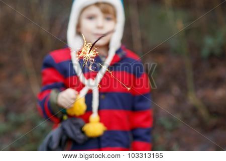 Little Child In Winter Clothes Holding Burning Sparkler