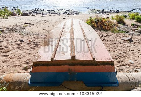 Old Rowboat Lays On A Sandy Coast
