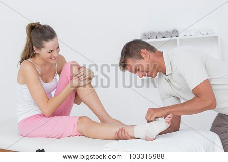 Doctor bandaging his patient ankle in medical house