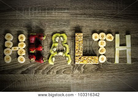 The Word Health Written With Fruits On A Wooden Background.