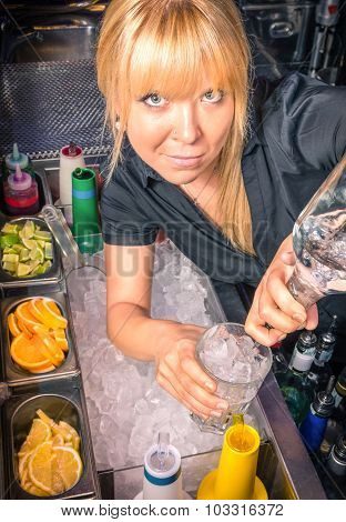 Beautiful Blonde Barmaid At Work Pouring A Cocktail In A Mixing Glass