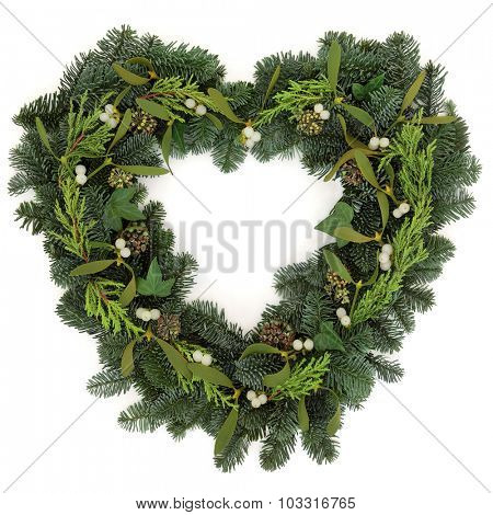 Heart shaped christmas wreath with mistletoe, ivy and winter greenery over white background.