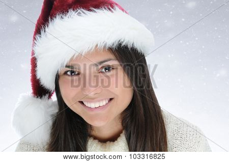 Closeup portrait of a happy young teenage girl wearing a Santa Claus Hat. Horizontal format with a snowy background.