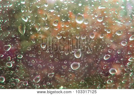 Raindrops On Glass. Color Blurred View Outside The Window.