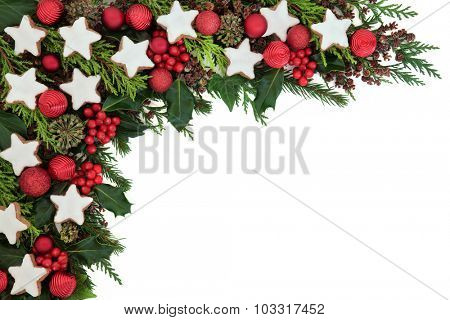 Christmas background border with gingerbread star biscuits, bauble decorations, holly, ivy, pine cones, cedar cypress and fir over white.