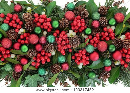 Christmas flora with red bauble decorations, holly, ivy, mistletoe, blue spruce fir and cedar cypress greenery.